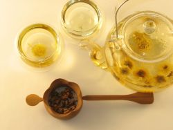 Chrysanthemum blossom tisane steeped in Glass Teapot with Metal Handle and Double Layered Glass Cups. Loose blossoms (unsteeped) in Bamboo Strainer with Long Handle.